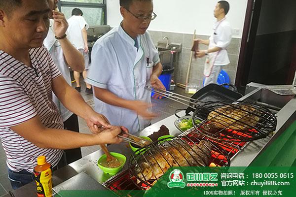 烤鱼培训班  老师正在手把手教学员烤鱼